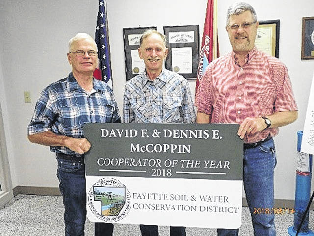 FSWCD Supervisor Jim Garland (left) presents the Cooperator of the Year award to Dennis and David McCoppin.