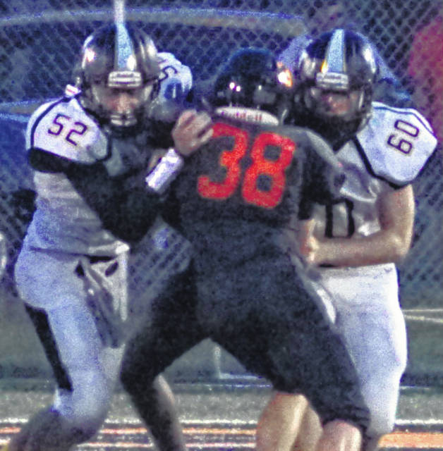 Miami Trace's Luke Henry (52) and Dylan Arnold (60) team up against Wilmington's Connor Mitchell (38) during a non-conference game at Wilmington Friday, Aug. 31, 2018.