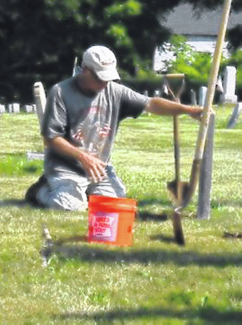 Mike Ferguson resetting an old tombstone in Bloomingburg Cemetery.