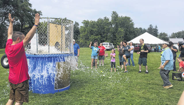 Pastor Andrew Johnson cheers as Cody Bowen is knocked into the dunk tank at the CommUNITY event on Saturday.