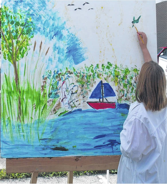 This Saturday — at 105 N. Main St. — artists from the community will spend the day showcasing their artistic abilities painting mural-sized canvases for the second-annual Art on the Square. Pictured is an artist from last year's event.