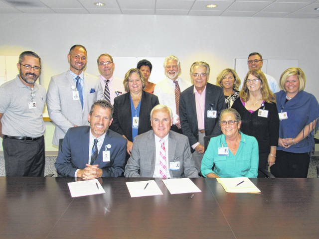 Fayette County Memorial Hospital's CEO Mike Diener, Adena Health System President & CEO Jeff Graham, and Adena Board of Trustees Chair Virginia Wettersten sign an affiliation agreement between the two, independent health care providers. Members of FCMH and Adena leadership teams are also pictured.