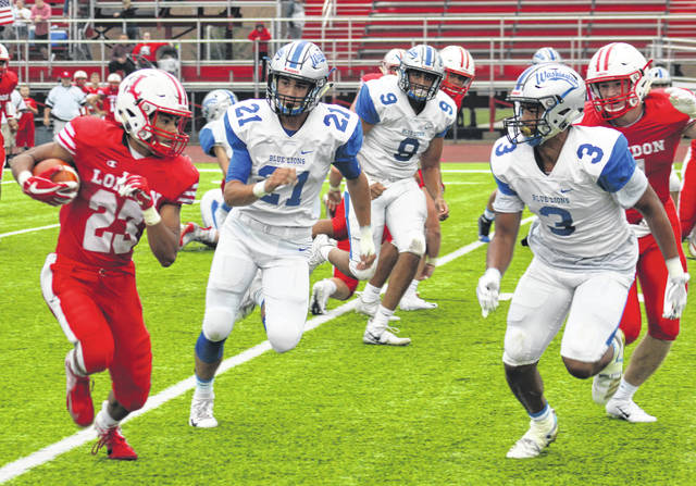 Washington Blue Lion defenders (l-r); Elisha Shaw (21), Jalen Pettiford (9) and Omar Porter (3) pursue London running back K.J. Price (23) during a non-conference game at London High School Friday, Sept. 7, 2018.