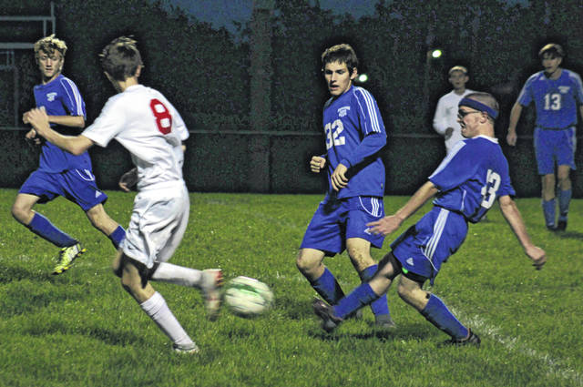Allan Schreckengaust (43) drives the ball forward for Washington in a Frontier Athletic Conference match against Jackson Thursday, Sept. 27, 2018. Also pictured for Washington (l-r); Reilly Downing, Ryan Schwartz (32) and Trent Langley (13).