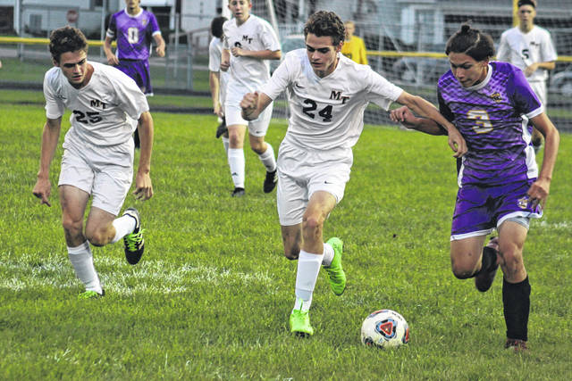 Miami Trace's Henry DeBruin (24) vies for control of the ball against Luke Sanchez of McClain during a Frontier Athletic Conference match Tuesday, Sept. 25, 2018 at McClain High School. Also pictured for Miami Trace is Simon DeBruin (25).