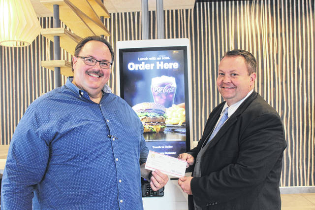 Matt Stanley (right), director of the Washington High School Marching Band, accepted a $600 check from Nick Epifano, owner/operator of McDonald's of Fayette County at the McDonald's on Elm Street Wednesday afternoon. The money was raised from kiosk sales on the first day of the grand opening of the new building on Aug. 25. Stanley thanked Epifano for his donation and continued support, and said the money will be spent replacing uniforms and helping to pay for a trip to Disney next spring.
