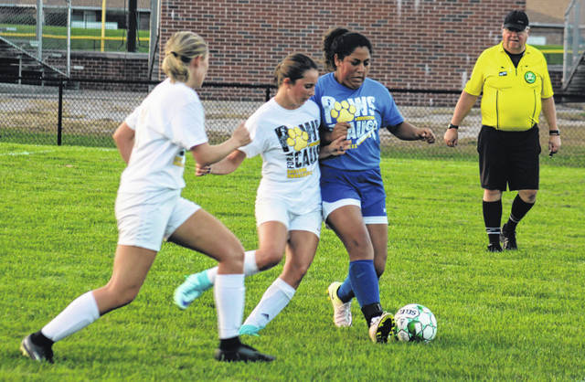 Miami Trace's Reagan Barton (middle) battles Washington's Maria Medina for possesion during a Frontier Athletic Conference match at Washington High School Tuesday, Sept. 18, 2018. Also pictured for Miami Trace, at left, is Tori Evans.