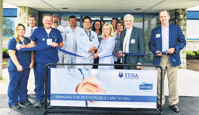 YUSA and Adena leaders and staff join to officially open the new on-site clinic at YUSA. From left to right, Heather Williams; Gene Rau; Randy Taylor; Duane Shipley; Brice Graham; CEO/ President YUSA Mitch Minamibata; Tiffany Castor; Dr. Ross; Rhonda Hassman; Beth Blair; Adena President/ CEO Jeff Graham; Steve Keating.