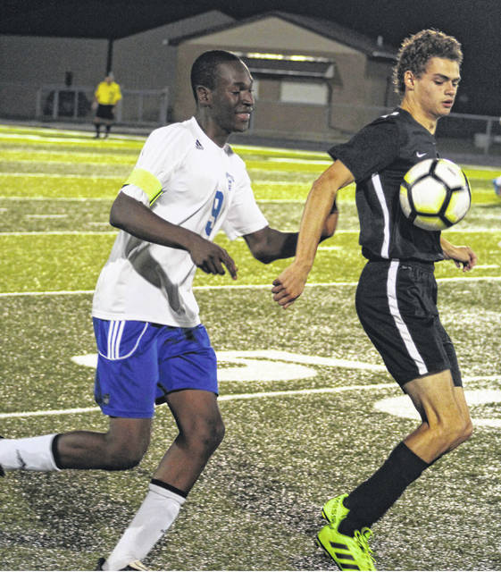 Blaise Tayese of Washington (left), defends as Miami Trace's Henry DeBruin looks to settle the ball during a Frontier Athletic Conference match at Miami Trace High School Thursday, Oct. 4, 2018.