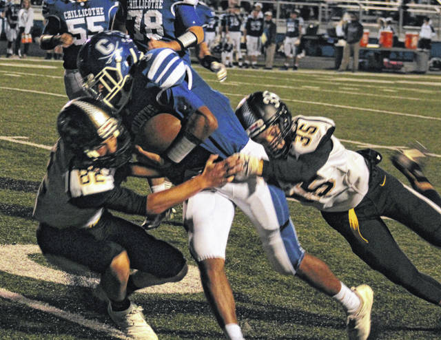 Miami Trace's Gage Miller (82) and Caden Sweitzer (35) combine to bring down the Chillicothe ball-carrier during a Frontier Athletic Conference game at Chillicothe Friday, Oct. 12, 2018.