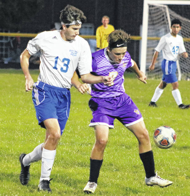 Washington's Trent Langley (13) defends as McClain's Caleb Goddard (7) tries to settle the ball during a Frontier Athletic Conference match at McClain High School Tuesday, Oct. 2, 2018. McClain won the match, 9-1.