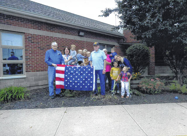 VFW Post 3762 donated a flag to Fayette Progressive Schools. Pictured (L to R): Bob Malone, Brenda Whitmer, Tom Smith and kids from the school.