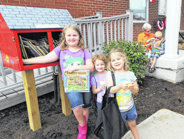 In mid-2016 the Washington C.H. Altrusa club got its Little Free Library project off and running. This two-year-old photo taken during the July 2016 Bloomingburg Community Days shows three Bloomingburg youngsters enjoying the treasures inside the well-crafted box set next to the Town Hall. At the request of Altrusan Janet Martin, Miami Trace High School teacher Bruce Bennett had encouraged two of his creative FFA students to construct the library box.