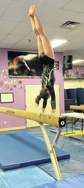 Miami Trace's Alyssa Butler balances a perfect handstand on the beam during a quad meet at Tric's Gymnastics Academy Friday, Dec. 21, 2018.