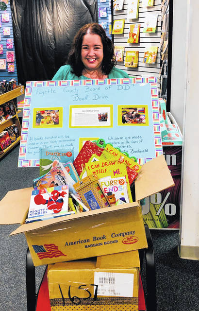 Sylvia Call, the early intervention service coordinator with FCBDD, with all of the books that were donated during the book drive.