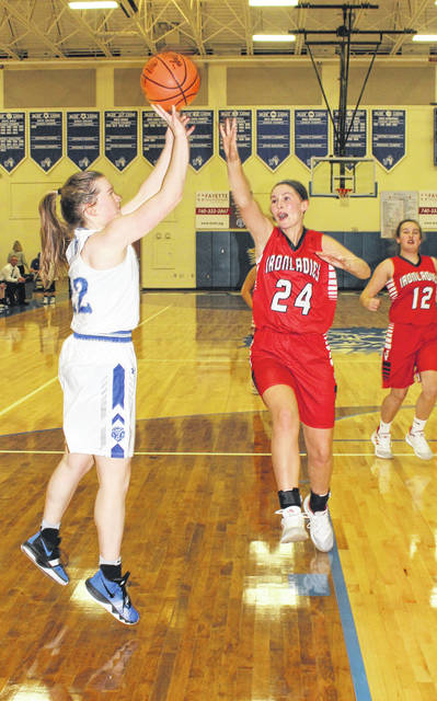 Washington junior Halli Wall puts up a shot defended by Jackson's Taylor Evans (24) during a Frontier Athletic Conference game at Washington High School Saturday, Dec. 8, 2018. Pictured at right for Jackson is Gracie Walburn (12).