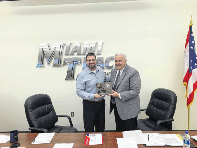 Miami Trace Superintendent David Lewis (left) presents school board member Mike Henry with a plaque for his service as board president in 2018.
