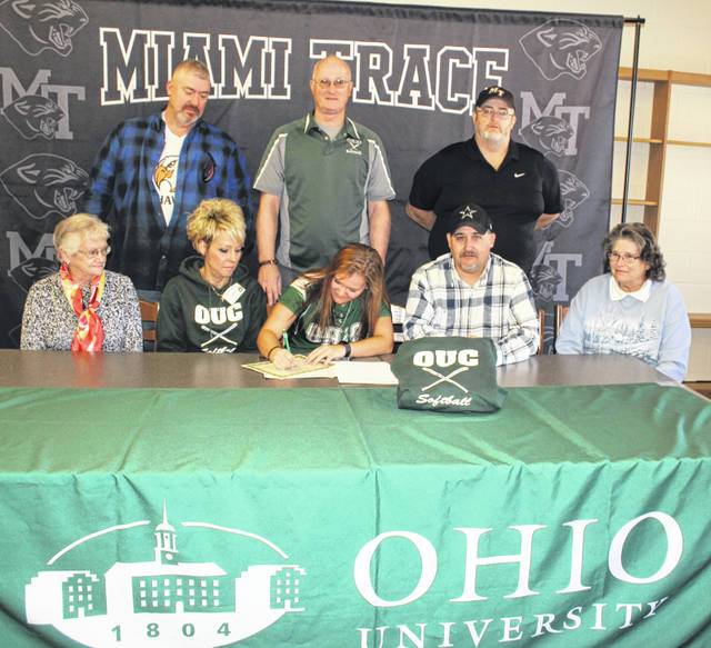 Miami Trace senior Breanna Eick, seated, middle, signs a letter of intent to attend Ohio University-Chillicothe where she will continue her education and her softball career. She was joined for the occasion by family members, coaches and teammates in the Miami Trace High School library. (front, l-r); Joy Altiers, great-grandmother; Susan Henry, mom; Eick, her dad, Chuck Eick and her grandmother, Sandy Adkins; (back, l-r); Tim Adams, travel coach for the Ohio Hawks; George Beck, Ohio University-Chillicothe softball coach and Joe Henry, Miami Trace softball coach.