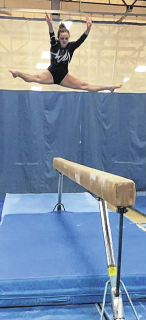 Maddy Southward skies high over the balance beam performing a straddle jump. Southward placed third in the event.