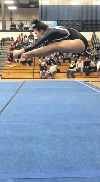 Milana Macioce executing a pike jump on floor exercise.