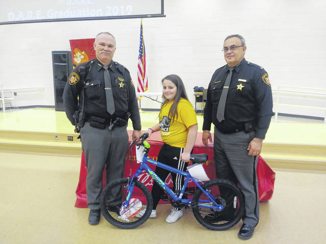 Miami Trace Elementary School celebrated its fifth graders' graduation from the D.A.R.E. program on Wednesday. Fayette County Sheriff's Office Deputy Monty Coe, their D.A.R.E. officer, and Sheriff Vernon Stanforth are pictured with first-place essay winner, Gabby Matthews.