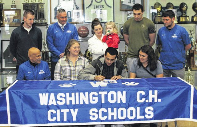 Washington High School senior Jalen Pettiford made it official when he signed a letter of intent to attend Thomas More University, where he will continue his education and his athletic career as a member of the Saints' football team. (front, l-r); coach John Jackson, mom Carrie Ragland, Pettiford, sister Trinity Ragland; (back, l-r); coach Cameron Pavey, head football coach Chuck Williamson, Maggie McDonald (holding Kinley Pettiford), Cedric Pettiford and coach Ryan Flora.