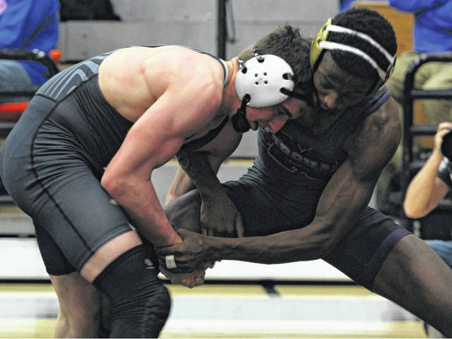 Miami Trace sophomore Mcale Callahan (left) wrestles Thurgood Marshall senior Ayyoub Muhammed in the match to determine third and fourth place at the District meet Saturday, March 2, 2019 at Wilmington High School. Callahan won this match, 1-0.
