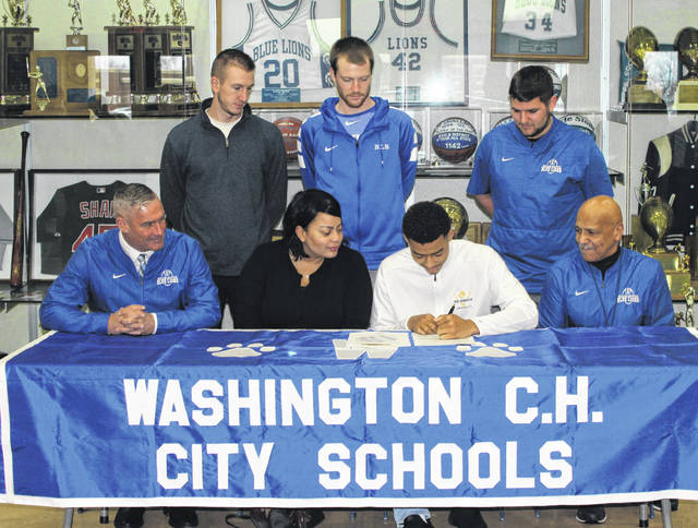 Omar Porter, seated, third from left, signs a letter of intent to attend Ohio Dominican University, where he will continue his education and his athletic career as a member of the Panthers' football team. (front, l-r); Washington Blue Lion head football coach Chuck Williamson, Porter's mother, Christina Cameron, football coach John Jackson; (back, l-r); assistant basketball coach Cameron Pavey, Blue Lion head basketball coach Connor Scott, and football coach Ryan Flora.