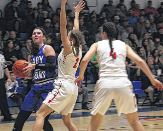 Washington junior Shawna Conger gets around a defensive double-team from Julia Ross (2) and Kate McEwan (4) of New Philadelphia during a Division II Regional semifinal game at Zanesville High School Tuesday, March 5, 2019.