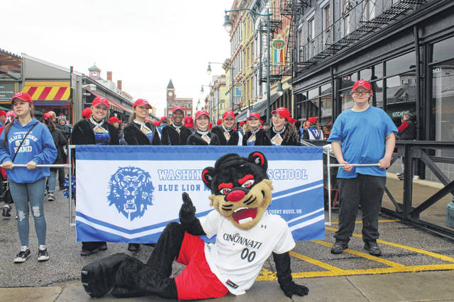 The Washington High School Blue Lion Marching band participated in the Cincinnati Reds opening day parade. First in line to represent Washington Court House were concert band members Gianna McManus (left) and Brayden Fowler (right) who carried the banner during the march. Directly behind them is the Rhythm and Blue Dance Team: (L-R) Haley Hixson, Jocelyn Trimmer, Amya Haithcock, Courtney Southworth, Makenzie Wise, Brooklynn Stanley and Ali Evans. Not pictured: Mackenzie Truex. Posing with the band is the University of Cincinnati Bearcats mascot.