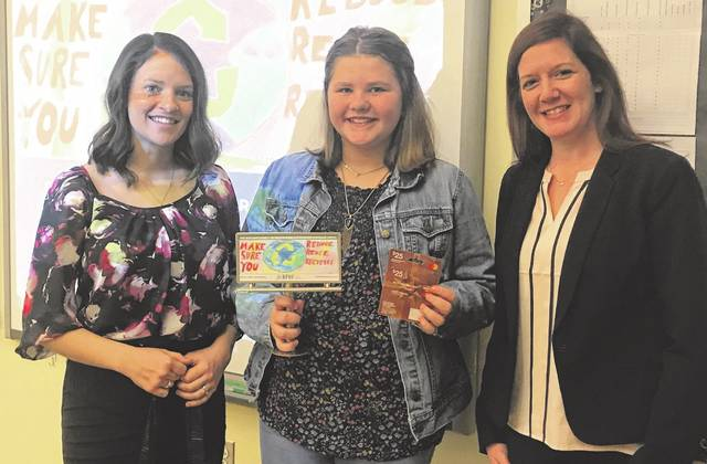 Adrienne Jacobson (pictured in the middle) is a fifth grade student at Miami Trace Elementary. Jacobson won first place for Fayette County in a contest hosted by RPHF Solid Waste District. The contest involved fifth graders in Ross, Pickaway, Highland and Fayette counties creating an informative billboard to encourage recycling. As the Fayette County winner, Jacobson's image will appear in April on the digital billboard at 1195 St. Route 22 West, near the Fayette County Fairgrounds. On Thursday, Erica Tucker and Lauren Grooms from the Solid Waste District, presented Adrienne with a replica of the billboard that she created along with a $25 gift card.