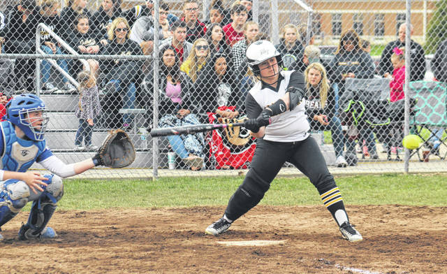 Aubrey Schwartz is about to connect for a basehit that drove in a run for Miami Trace in their game against Washington Friday, April 12, 2019 at Miami Trace High School. At left for Washington is catcher Maddy Jenkins.
