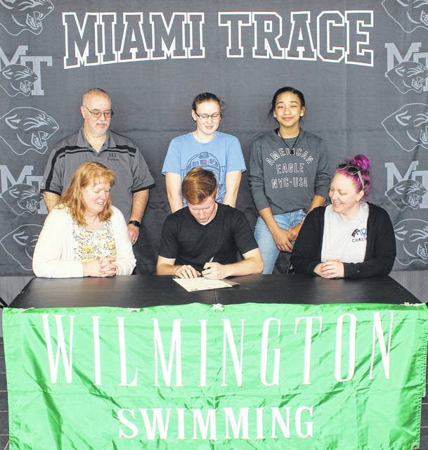 Isaac Abare, seated, middle, signs a letter of intent to attend Wilmington College where he will continue his education and his swimming career. Joining Abare for the occasion (front, left), his mother, Janet Abare and at right, swim coach Katie Kasberg and in back, (l-r); his father, Andrew Abare and his sisters, Debbie and Lydia Abare.