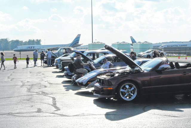 Visitors to Laurel Oaks, like these recent car show participants, often see planes next to the school's parking lot.