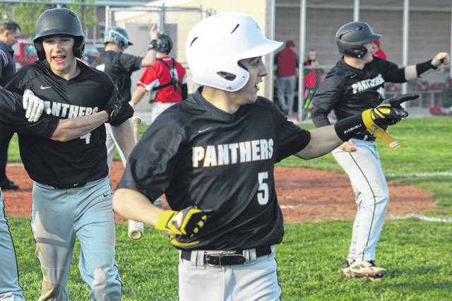 Miami Trace's Connor Bucher, left, is greeted while teammates Cody Brightman (5) and Drew Batson (right) gesture to Dalton Mayer at second after Mayer drilled a three-run double in the bottom of the sixth that lifted the Panthers to a 9-6 win over FAC-leaders Hillsboro Monday, April 29, 2019 at Miami Trace High School.