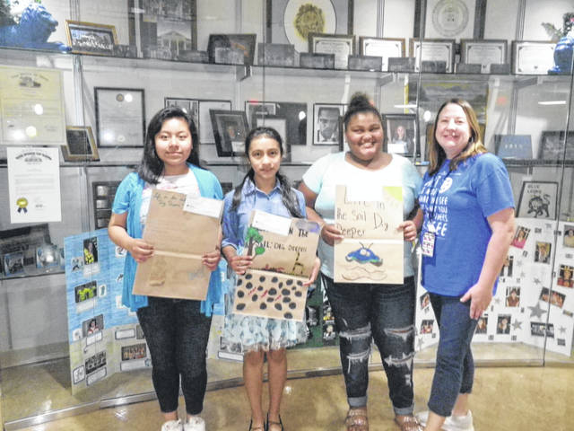 The poster contest winners were: first place, Yadira Molina-Lopez, second place, Jessica Lopez Dominguez, and third place, Jada Ryan. Also pictured is Washington Middle School art teacher Tami Rose.