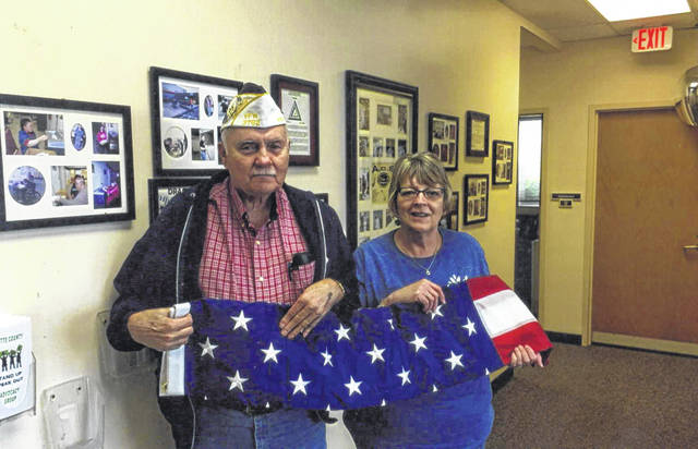 The VFW Post 3762 donates a flag to Fayette Progressive Industries. Pictured (L to R): Bob Malone and Vicky Clay.