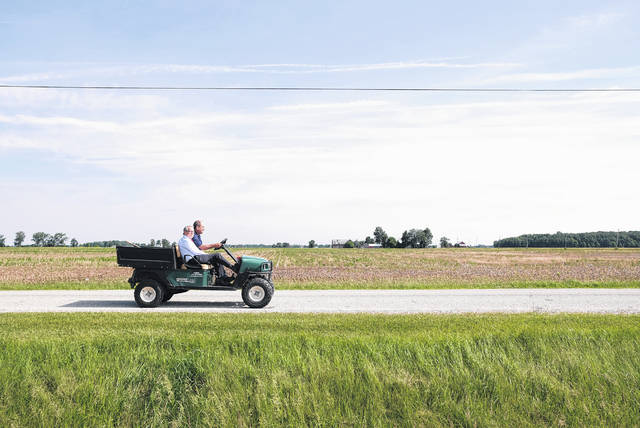 Ohio Gov. Mike DeWine rides in a farm vehicle along Reitz Road with local farmer Kris Swartz near his Perrysburg Township home Wednesday morning.