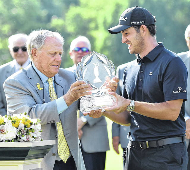 Memorial Tournament host Jack Nicklaus (left) hands the championship trophy to Patrick Cantlay.