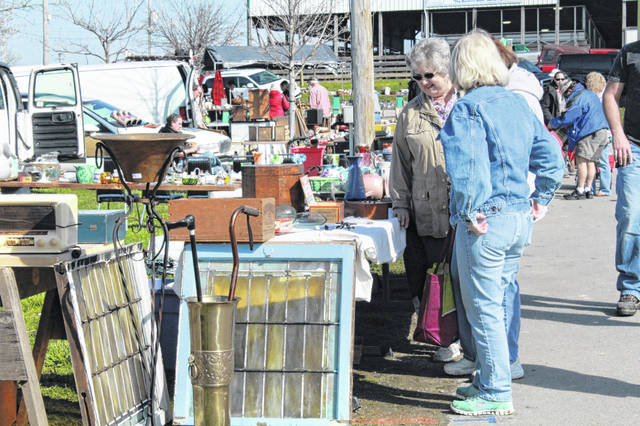 Customers browse through a row of booths at Scott Antique Markets in the Fayette County Fairgrounds.