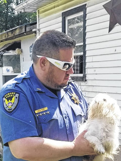 Brad Adams, humane agent for Fayette County Regional Humane Society, taking part in the joint rescue effort in Pike County after the owner's death left behind numerous dogs—approximately 52 dogs were removed by the FRHS, RCHS, Pike County Sheriff's Office and the Pike County Dog Warden.