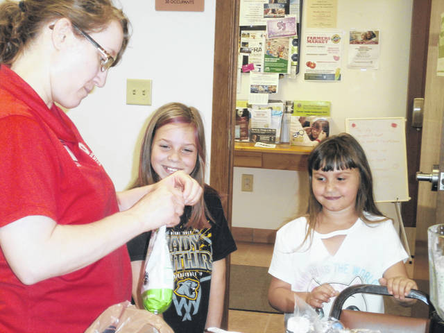 Hayley and Ryleigh make a martian smoothie with Sarah Sowell, Fayette County OSU's Program Assistant SNAP-ED, at Jeffersonville Branch Library. Sarah also showed the attendees how to make bananas in a blanket, apple yogurt wraps and sweet potato chocolate chip bars.
