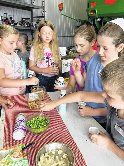 Adailya, Abby, Breanna, Annabel, and Anthony taste soybeans in different forms.