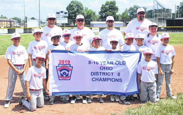 2019 DISTRICT 8 CHAMPION WASHINGTON C.H. 10-YEAR-OLD ALL-STARS — The team stands with its championship banner after a 12-11 win over Eaton at Eaton Saturday, July 20, 2019. (kneeling at left), Quinton Marine; (kneeling at right, Kiontae Tyree; (standing, l-r); James Bunch, Sam Pfeifer, Liam Alsop, Kolton Pennington, Kenton Berry, Corbin Evans, Matthew Jones, Nathaniel Brown, Carter Davidson, Jacob Hays, Hayden Cornell; (back, l-r); manager Matt Pfeifer, coaches Todd Cornell, B.J. Marine and Ken Berry.