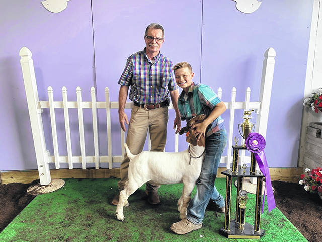 Corbin Melvin (right) won the grand champion Boer market goat for the second year in a row at Tuesday's Fayette County Junior Fair goat show. He is pictured with the judge of the show, Jim Wilson.
