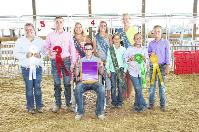 Zander Ivey (seated) won the overall hog showman prize for the second straight year Tuesday at the Fayette County Junior Fair hog showmanship contest. Joining Ivey from left to right are other showmanship winners and fair royalty: third place winner Kasi Payton, second place winner Kylan Knapp, Fayette County Fair Queen Abbi Pettit, Fayette County Fair First Attendant Tori Evans, Fayette County Pork Princess Allison Reeves, Fayette County Fair Attendant Andrea Robinson, fifth place winner Maya McCoy, and fourth place winner Aiden Knecht.