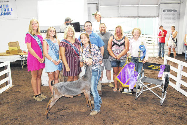 Kelsey Pettit's grand champion dairy goat sold for $1,000 Thursday evening at the Fayette County Fair Dairy Goat Sale. Pettit is pictured with the buyers and fair royalty, from left to right: Fayette County Fair Attendant Andrea Robinson, Fayette County Fair First Attendant Tori Evans, Fayette County Fair Queen Abbi Pettit, Doug Shannon of Merchants Bank, Greg Pettit of Pettit Enterprise, Lisa Pettit of Pettit Enterprise, and Mara Simonson, a friend.