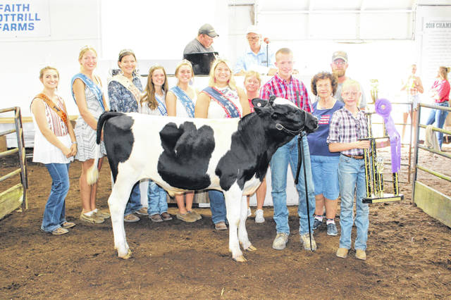 Matthew Webb's grand champion dairy feeder sold for $900 Friday at the Fayette County Fair Dairy Feeder Sale. Webb is pictured with buyers and fair royalty, from left to right: Fayette County Beef Queen Macie Riley, Fayette County Fair Attendant Andrea Robinson, Fayette County Lamb & Wool Queen Tapanga Sanderson, Fayette County Dairy Princess Abby Riley, Fayette County Fair First Attendant Tori Evans, Fayette County Fair Queen Abbi Pettit, mother Robin Webb, Judy Craig of the Fayette County Democrats, father Brian Webb, and sister Elizabeth Webb.