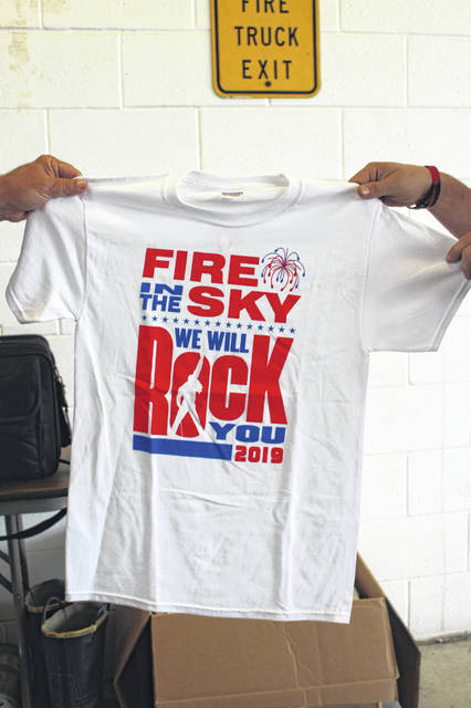 Two volunteers show off the 2019 Fire In The Sky t-shirt available for a $5 donation. Volunteers, as well as coordinator Dan Fowler, said they are still looking for donations to keep the show running in 2020.