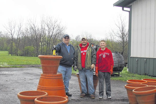 Three generations of Master Gardeners prepare the containers for this year's flowers. Pictured (L to R): master gardener Charlie Crutcher, Intern Keith Crutcher and future master gardener Landon Crutcher.